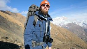 Een gebaarde mens in zonnebrilhoed met een rugzak en een camera bevindt zich hoog in de bergen en kijkt op de zijlijn stock videobeelden