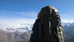Een gebaarde mens in zonnebrilhoed met een rugzak en een camera bevindt zich hoog in de bergen en kijkt op de zijlijn stock footage