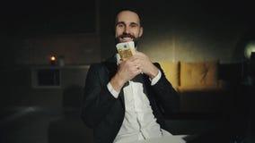 Een gebaarde zakenman werkt thuis met laptop en houdt een groot pakje van contant geld Een volwassen mens glimlacht Hij is gelukk stock footage
