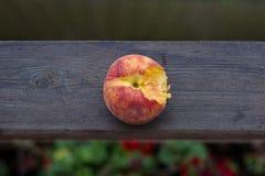 Een gebeten perzik op een houten achtergrond in aard Stock Foto