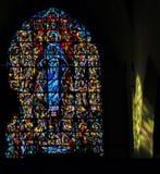 Een Gebrandschilderd glasvenster met kleurrijke zonnestraal die op een muur in een kerk in België glanzen royalty-vrije stock afbeelding