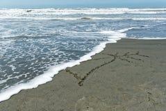 Een gebroken die hart, wordt een hart in het zand wordt getrokken gesneden in de helft door een inkomende golf royalty-vrije stock foto