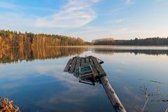 Een gebroken pier op een meer in het bos stock foto's