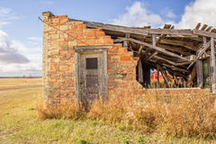 Een gedeeltelijke bakstenen muur met een grijze deur Stock Foto