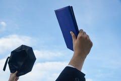 Een gediplomeerde die de graad en de gediplomeerde hoed opheffen royalty-vrije stock afbeeldingen