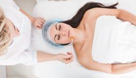 Een geduldige vrouw met gesloten ogen ligt in de spreekkamer Kosmetische procedures in de kosmetiekbureau Gezicht van stock afbeelding