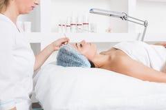 Een geduldige vrouw met gesloten ogen ligt in de spreekkamer Kosmetische procedures in de kosmetiekbureau Gezicht van royalty-vrije stock fotografie
