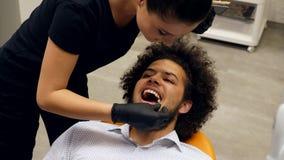 Een geduldige zitting in tandartsen zit en wachten voor de tandartsenmedewerker voor om de juiste schaduwkleur van zijn tanden te stock videobeelden