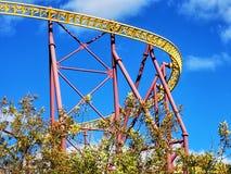 Een geel en rood achtbaanspoor tegen een diepe blauwe hemel royalty-vrije stock afbeeldingen