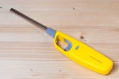 Een geel gas lichter kanon op een houten lijst royalty-vrije stock foto's