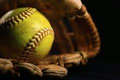 Een geel softball in een oude, bruine, leerhandschoen stock afbeelding