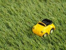 Een geel stuk speelgoed parkeerterrein op groen grasgebied Royalty-vrije Stock Afbeelding