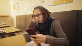 Een gefrustreerd jong ongeduldig meisje in glazen mist de koffie De vermoeide vrouw wacht op de vriend en is bored stock footage