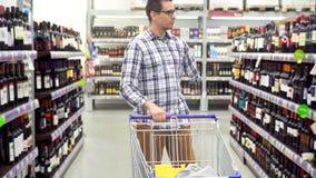 Een gehandicapte mens in een plaidoverhemd met een geamputeerd wapen in een winkel met een boodschappenwagentje stock footage