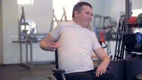 Een gehandicapte mens rekt zijn wapens en schouders uit terwijl het zitten in een rolstoel stock footage