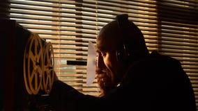 Een geheime speciale agent luistert aan het gesprek met een geleide microfoon stock footage