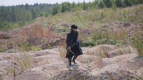 Een geheimzinnige mens in een zwarte mantel en een hoed loopt door de woestijn stock videobeelden