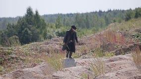 Een geheimzinnige mens in een zwarte regenjas en een hoed beklimt een kleine heuvel en loopt verder door de woestijn stock videobeelden