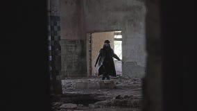 Een geheimzinnige mens in een zwarte regenjas en een hoed en glazen gaat door de gebroken ruimten van een verlaten fabriek over stock video