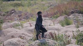 Een geheimzinnige mens in een zwarte regenjas en een hoed loopt langzaam door het woestijn verlaten gebied onder de schroeiende z stock videobeelden