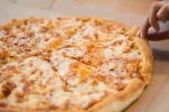 Een gehele vier kaaspizza op een eettafel royalty-vrije stock afbeeldingen