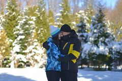 Een gehuwd houdend van paar die rond in een sneeuwbos op de Zonnige winter voor de gek houden stock foto