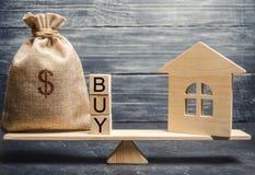 Een geldzak en houten blokken met het woord kopen en een miniatuurhuis op schalen De accumulatie van geld voor de aankoop van stock foto's