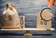 Een geldzak en houten blokken met het woord kopen en een miniatuurhuis op schalen De accumulatie van geld voor de aankoop van stock foto