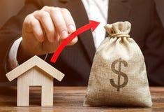 Een geldzak en een rode pijl in de handen van een mens dichtbij een huis Het concept de groei van de onroerende goederenmarkt Pri stock foto