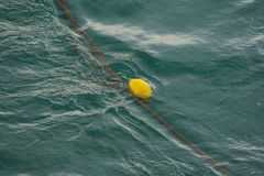 Een gele boei die in het overzees drijven stock afbeeldingen