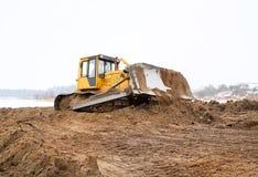 Een gele bulldozer die in de winter werkt Stock Afbeelding