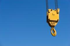 Een gele die kraanhaak tegen een blauwe hemel wordt opgeschort Stock Foto's