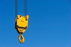 Een gele die kraanhaak tegen een blauwe hemel wordt opgeschort Royalty-vrije Stock Afbeeldingen