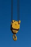 Een gele die kraanhaak tegen een blauwe hemel wordt opgeschort Royalty-vrije Stock Afbeelding