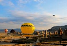 Een Gele hete luchtballon ongeveer om op het grote gebied te vliegen stock afbeeldingen