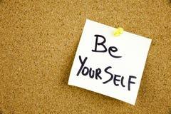 Een gele kleverige nota die, titel, inschrijving is uw beste zelf - positieve woorden op een leibord in zwart Ext. schrijven stock afbeelding