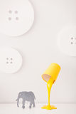 Een gele lamp in de vorm van een emmer van verf is op een witte nightstand Dichtbij is een beeldje van een grijze olifant In Stock Afbeelding