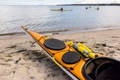 Een gele overzeese kajak op het zand en vier die langs de kust kayaking Royalty-vrije Stock Foto's