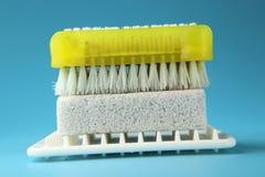 Een gele plastic borstel voor het schoonmaken en stuk zeep op wit onderleggertje royalty-vrije stock fotografie