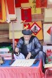 Een geleerde schrijft Chinese kalligrafiekarakters bij Tempel van Literatuur Stock Afbeeldingen