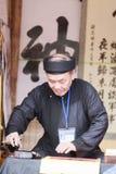Een geleerde schrijft Chinese kalligrafiekarakters bij Tempel van Literatuur Stock Afbeelding