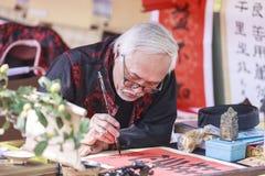 Een geleerde schrijft Chinese kalligrafiekarakters bij Tempel van Literatuur Royalty-vrije Stock Afbeeldingen