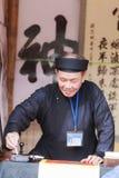 Een geleerde schrijft Chinese kalligrafiekarakters bij Tempel van Literatuur Stock Foto's