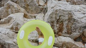 Een gelooid meisje in een zwempak en een hoed is maakt een grappige draai van een opblaasbare vlottercirkel op haar hand en kijkt stock videobeelden