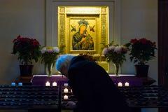 Een gelovige steekt een kaars dichtbij de pictogrammen van St. Mary aan. Royalty-vrije Stock Foto