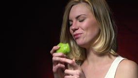 Een gelukkig blonde in een witte T-shirt eet kiwi stock footage