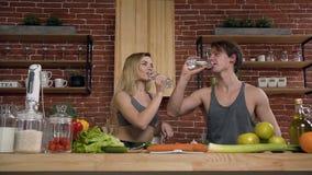Een gelukkig geschikt paar bereidt voedsel in de keuken voor die met flessen en drinkwater in de keuken thuis klikken stock footage