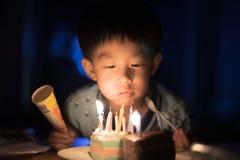 Een gelukkig jong geitje blaast kaarsen op zijn verjaardagscake bij zijn nacht van de verjaardagspartij stock afbeeldingen