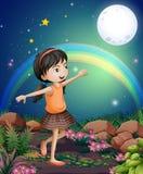 Een gelukkig jong meisje die dichtbij de bloemen spelen Stock Foto's