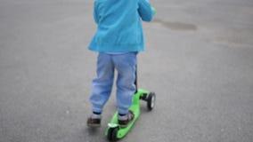 Een gelukkig kind berijdt zijn autoped in het Park Pret in openlucht blur stock video